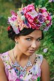 Junge attraktive Frau mit Krone von Blumen Stockfotografie