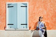 Junge attraktive Frau nahe der Wand mit Fenster Lizenzfreie Stockfotografie