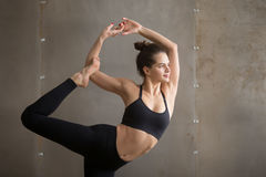 Junge attraktive Frau in Natarajasana-Haltung, graues Studio backgro stockfotografie
