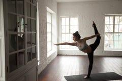 Junge attraktive Frau in Natarajasana-Haltung, weißes Dachbodenstudio b stockfotografie