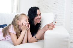 Junge attraktive Frau und süße kleine blonde das Kind, die digitale Tablette hält, füllen aufpassendes Internet zusammen auf Lizenzfreie Stockbilder