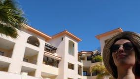 Junge attraktive Frau, welche die Sonne genie?t und tragenden Hut und Sonnenbrille mit Palmen auf dem Hintergrund aufwirft Hotelg stock video footage