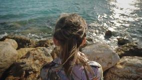 Junge attraktive Frau, welche die Sonnenuntergangsonne sitzt auf einem felsigen Seeufer betrachtet Das Haar, das im Wind flattert stock video