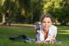 Junge, attraktive Frau zeigt ihr smartphone Lizenzfreie Stockbilder