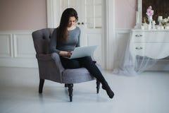 Junge attraktive Frau zu Hause, arbeitend mit Laptop, freie on-line-Klassen für Interesse, häusliches Mutterbeginnen Stockbild