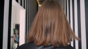 Junge attraktive Frauen mit schwerem bilden Sie einladen, weggehen und herum sich drehen, überzeugter, gestreifter Korridor stock footage