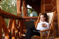 Junge attraktive Geschäftsfrau arbeitet an dem Laptop am Höhenkurort mit einer Tasse Tee und Plätzchen Frau entspannt sich Stockfotos