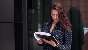Junge attraktive Geschäftsfrau betrachtet ein Geschäftsprojekt in den Dokumenten nahe bei dem Bürogebäude stock video