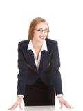 Junge attraktive Geschäftsfrau, die über Tabelle verbiegt. Lizenzfreies Stockbild