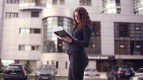 Junge attraktive Geschäftsfrau, die durch die Stadt läuft und Dokumente betrachtet stock video footage
