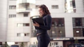 Junge attraktive Geschäftsfrau, die durch die Stadt mit den Dokumenten sprechen am Telefon läuft stock video footage