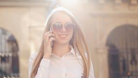 Junge attraktive Geschäftsfrau, die durch Straße im Finanzbezirk einer alten Stadt geht Sie sprechend durch intelligentes stock footage