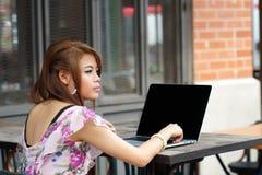 Junge attraktive Geschäftsfrau, die an ihrem Laptop an im Freien arbeitet Stockfotos