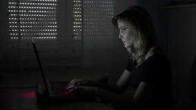 Junge attraktive Geschäftsfrau, die an ihrem Schreibtisch in einer Dunkelkammer schreibt und plaudert mit Kunden auf Laptop sitzt stock footage