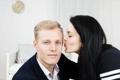 Junge attraktive Geschäftsfrau, die Mann in der Gesellschaftskleidung küsst lizenzfreie stockbilder