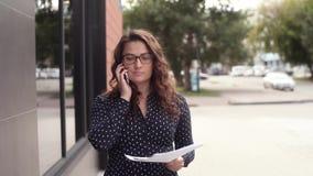 Junge attraktive Geschäftsfrau geht um die Stadt und wirft Dokumente oben mit einer guten Laune stock video footage
