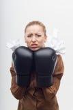 Junge attraktive Geschäftsfrau mit Boxhandschuhen Stockfoto