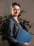 Junge attraktive Geschäftsfrau mit Faltblatt stockfotografie