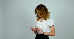Junge attraktive Geschäftsfraublicke auf ihre Uhr und Wartung einen Anruf, indem sie an einem Handy anstarren und verblaßt dann w stock video footage