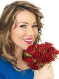 Junge attraktive glückliche Frau, die ein Bündel rote Rosen hält Stockbilder