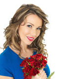 Junge attraktive glückliche Frau, die ein Bündel rote Rosen hält Lizenzfreie Stockfotos