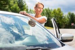 Junge, attraktive, glückliche Frau, die einen Koffer von ihrem Auto nimmt Lizenzfreie Stockfotografie