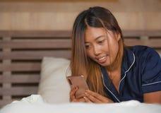 Junge attraktive glückliche und entspannte asiatische Jugendlichfrau im Bett der Pyjamas zu Hause unter Verwendung der Datierung  lizenzfreies stockfoto