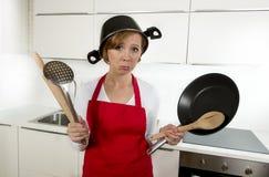 Junge attraktive Hauptkochfrau im roten Schutzblech an der Küche, die Wanne und Haushalt mit Topf auf ihrem Kopf im Druck hält Lizenzfreie Stockfotos