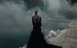 Junge attraktive Hexe, die auf die Brücke im schweren schwarzen Rauche geht lizenzfreie stockfotografie