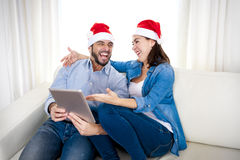 Junge attraktive hispanische Paare in Liebe on-line-Weihnachtskaufender digitaler Tablette lizenzfreie stockbilder