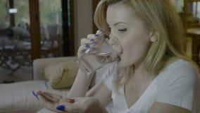 Junge attraktive Journalistfrau, die auf einmal zwei Antibiotikumpillen mit einem Glas der Kapsel des Wassers eins zu Hause schlu stock footage