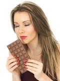 Junge attraktive junge Frau, die eine Milchschokolade-Stange hält Lizenzfreie Stockfotografie
