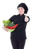 Junge attraktive Kochfrau in der schwarzen Uniform mit Gemüse THU Stockfotografie