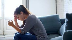 Junge attraktive lateinische Frau, die zu Hause Wohnzimmerliegt, Couch, die trauriger müder und besorgter leidender Krise in der  stock footage