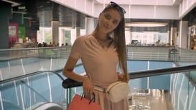 Junge attraktive Mädchen, die im Mall, Tragetaschen, aufpassend an der Kamera stehen und lächeln, Einkaufskonzept, Modekonzept stock video footage