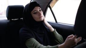 Junge, attraktive moslemische Frau, die ein hijab austauscht in einem Auto trägt Sie ist das Tragen die dunkle Kleidung und sitzt stock video