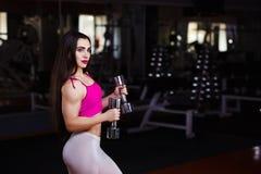 Junge attraktive muskulöse Eignungsfrau, die Übung mit stummem tut stockfotografie