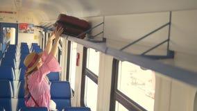 Junge attraktive Mutter mit der Tochter, die geht, in Geschwindigkeitszug zu reisen - setzt den Koffer auf das oberste Regal stock video footage