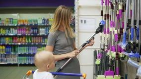 Junge attraktive Mutter wählt einen Bodenwischer im Supermarkt, während ihr kleines Kind in einem Lebensmittelgeschäftwarenkorb s stock footage