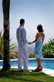 Junge attraktive Paare in den Liebesholdinghänden unter einer Palme Stockbild