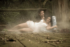 Junge attraktive Paare, die auf hölzerner Plattform im Wald flirten stockfotografie