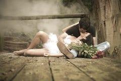 Junge attraktive Paare, die auf hölzerner Plattform im Wald küssen lizenzfreie stockfotografie