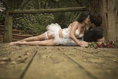 Junge attraktive Paare, die auf hölzerner Plattform im Wald küssen Stockbild