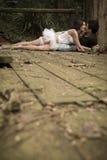Junge attraktive Paare, die auf hölzerner Plattform im Wald küssen Lizenzfreie Stockfotos