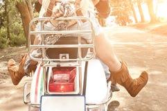 Junge attraktive Paare, die auf Roller entlang Schotterweg reisen lizenzfreie stockbilder