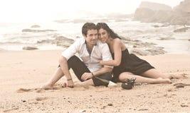 Junge attraktive Paare, die auf Strand lachen stockfotos