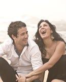 Junge attraktive Paare, die auf Strand lachen lizenzfreies stockfoto