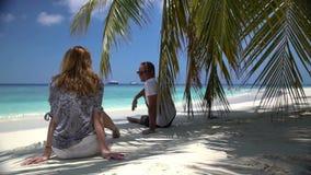 Junge attraktive Paare, die einen Feiertag auf der tropischen Küste genießen stock video footage