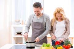 Junge attraktive Paare, die in einer Küche kochen Stockbild