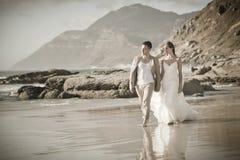 Junge attraktive Paare, die entlang tragendes Weiß des Strandes gehen Lizenzfreies Stockfoto